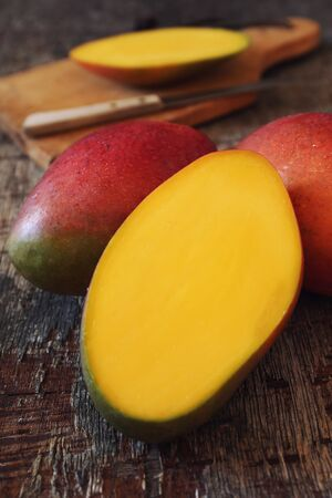 Tropical mango fruit, intact and half on wooden background. Selective focus Stock Photo