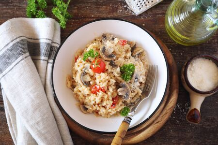 Italian cuisine. Plate of mushroom risotto with cherry tomatoes and parmesan cheese  on wooden background. Top view