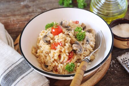 Italian cuisine. Plate of mushroom risotto with cherry tomatoes and grated parmesan cheese  on wooden background