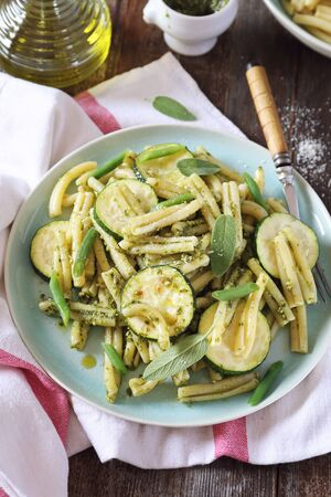 Italian penne pasta with roasted zucchini, pesto sauce and green beans, olive oil and sage dressing. Top view