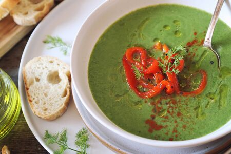 Green pea soup with spinach, olive oil, red grilled bell pepper and dill dressing. Rustic style, top view
