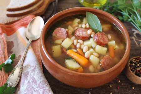 Spanish cuisine. Caldo gallego: traditional bean soup with seasonal vegetables and sausages in authentic clay bowl. Rustic style