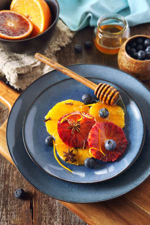 Citrus dessert. Orange carpaccio with honey, spices and blueberries from yellow and blood oranges, rustic style