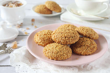 Homemade sesame cookies and cup of tea for sweet breakfast on light background