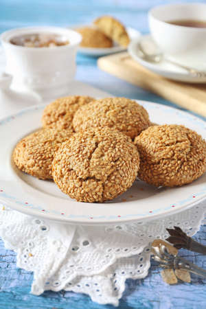 Homemade sesame cookies and cup of tea, sweet breakfast on blue background Stock Photo