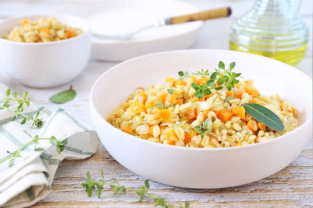 Pearl barley warm salad with carrots and fried onions, thyme garnish on light background