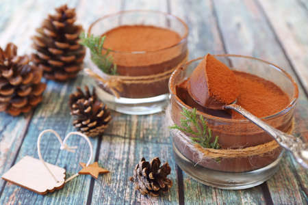 Two portions of chocolate mousse, cocoa powder dressing for New Year's holiday