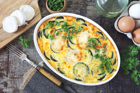 French cuisine. Vegetable zucchini clafoutis with goat cheese in ceramic bakeware. Top view
