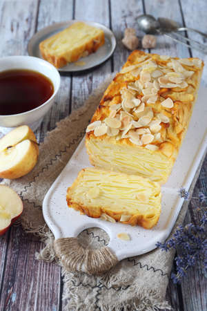 French cuisine. Invisible apple cake, almond petals dressing and cup of lavender tea. Top view