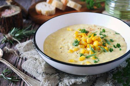 Corn Chowder. American cuisine. Creamy corn soup, green onions and parsley dressing. Rustic style Archivio Fotografico