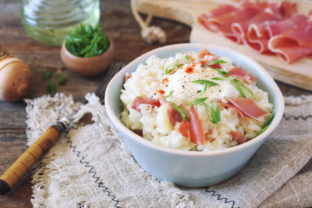Creamy risotto with parma ham (or prosciutto di Parma), green onion dressing on a wooden backgrounde, rustic style