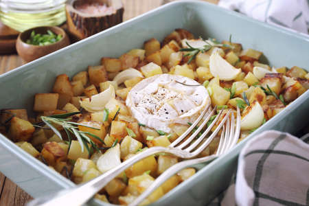 Fried potato cubes with camembert cheese, rosemary and green onion in ceramic cookware