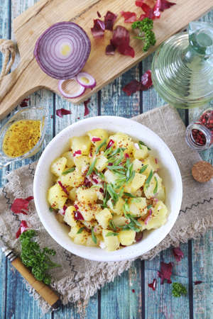 German cuisine. Potato salad with red and green onions, mustard and olive oil sauce. Top view