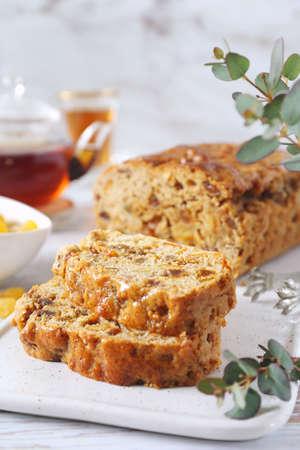 Traditional English tea raisins cake with candied orange, egg-free cake and cup of tea. Five clook tea