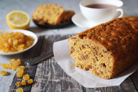 Traditional English tea raisins cake, egg-free cake and cup of lemon tea. Five clook tea, focus selective Archivio Fotografico