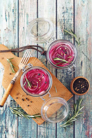 Pickled red onion salad in two jars, spices and rosemary. Top view Archivio Fotografico