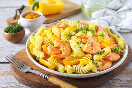 Spicy fusilli pasta with yellow pepper and red fried shrimps, parsley dressing