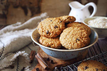 Homemade oatmeal cookies with chocolate drops on wooden background, rustic style