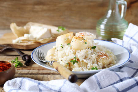 Italian cuisine. Plate of scallop risotto, olive oil and parmesan cheese on wooden background Archivio Fotografico