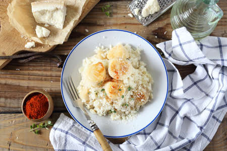Italian cuisine. Plate of scallop risotto, olive oil and parmesan cheese on wooden background. Top view