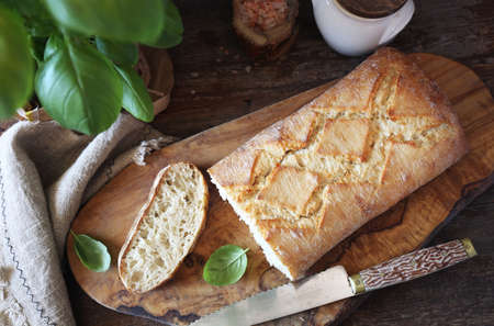 French country bread and basil on wooden chopping board, rustic style. Top view Archivio Fotografico