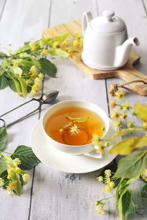 Cup of herbal linden tea with linden flowers on light background