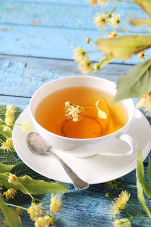 Cup of herbal tea with linden flowers on blue background