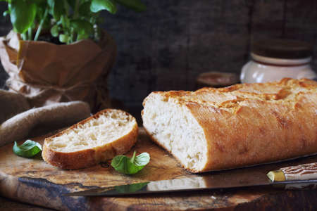 French country bread and basil on wooden chopping board, rustic style
