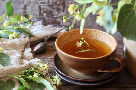 Cup of herbal tea with linden flowers on old wooden background