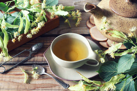 Cup of herbal tea with linden flowers on old wooden background. Toned image Archivio Fotografico
