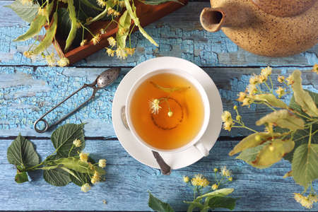 Cup of herbal linden tea with linden flowers on blue background. Top view Archivio Fotografico