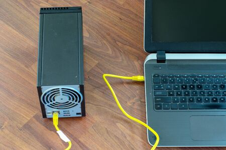 Laptop connected with NAS network device with yellow ethernet cable