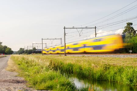 Dutch railway train with speed, with long exposure.