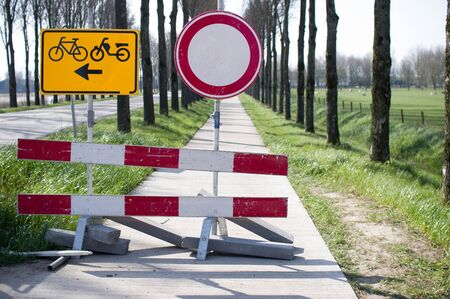 Road closed with barriers and sign for cyclists for roadworks