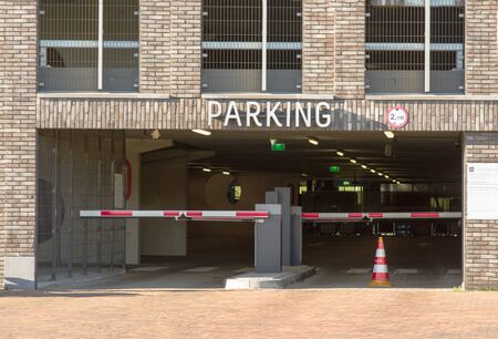 Entrance to a parking garage with closed barriers where cars are parked