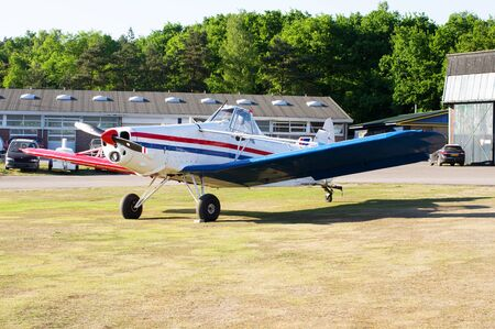 Small private sport plane on grass field on airport. Imagens