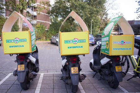 Arnhem, Netherlands - October 29, 2019:Scooters for delivery of pizzas viewed from the back, New york pizza is a dutch fast food chain specializing in pizzas Redactioneel