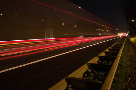 Highway at night with traffic blurred by motion with guardrail in the foreground in Arnhem, Netherlands