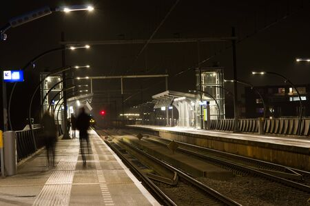 People blurred by motion at station Arnhem south at night, Netherlands