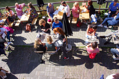 Utrecht, Netherlands - September 14, 2019: People relaxing and drinking at an terrace on a quay, seen from above.