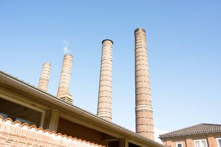 Four old industrial chimneys with clouds and smoke