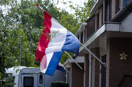 Dutch flag waving in the wind on a facade of a house during a national holiday in the Netherlands Banque d'images