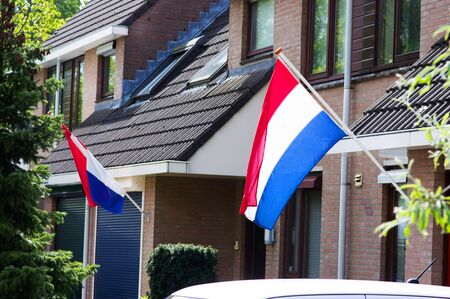 Two dutch flags waving in the wind on a facade of a house during a national holiday in the Netherlands