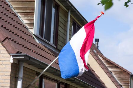 Dutch flag on a facade of a house during a national holiday in the Netherlands
