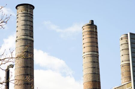 Three old industrial chimneys with clouds and smoke