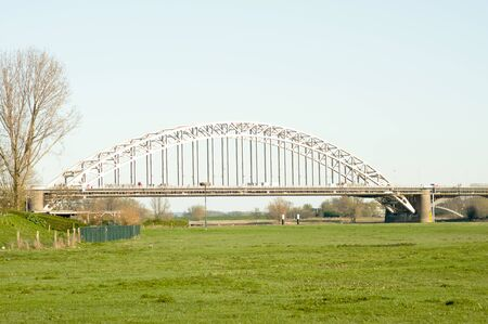 Waalbrug over the river the Waal, with in the foreground a meadow in Nijmegen, Netherlands