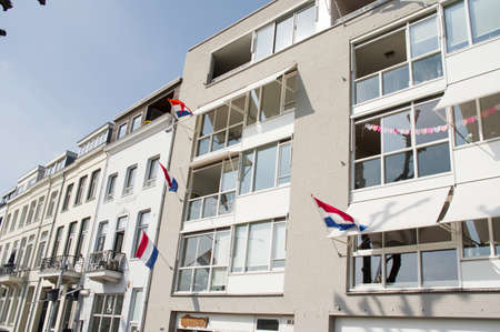 Arnhem, Netherlands - April 27, 2020: Multiple dutch flags waving in the wind on a facade of apartments during a national holiday in the Netherlands