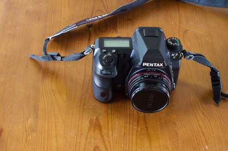 Arnhem, Netherlands - May 15, 2020: Pentax K-3 II camera body with a 21 mm lens on a wooden table Éditoriale