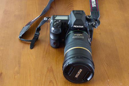 Arnhem, Netherlands - May 15, 2020: Pentax K-3 II camera body with 200 mm lens on a wooden table