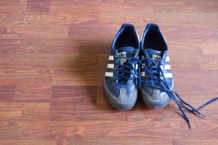 Arnhem, Netherlands - May 20, 2020: Pair of used blue Adidas sneakers on a wooden floor